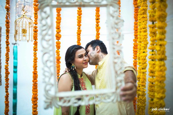 Mehendi photobooth with frames bird cages and genda flower backdrop