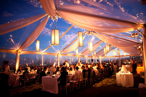 Tent outdoor wedding reception decorations with thin hanging lanterns and long tables and small wooden chairs