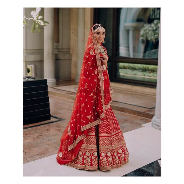 ac73a4c9c795 Sabyasachi's statement red bridal ensemble with gorgeous golden embroidery  spread all over the lehenga and big floral patterns embroidered on the  blouse.